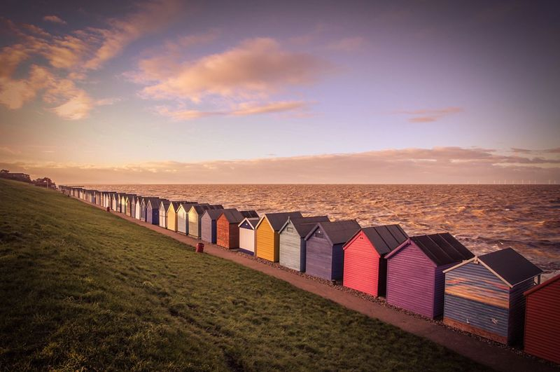 Colorful beach huts on beach against cloudy sky