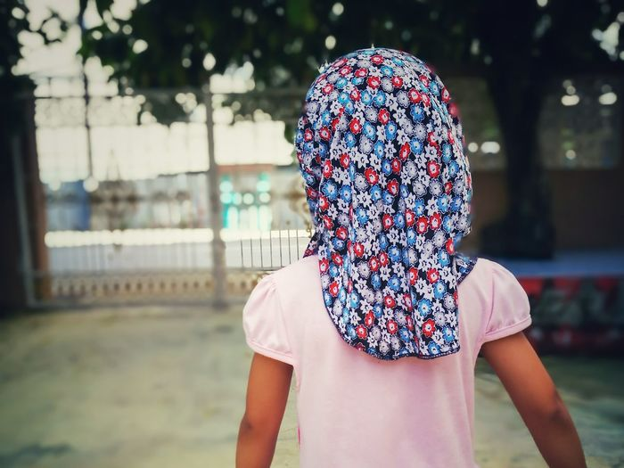Rear view of girl wearing floral headscarf