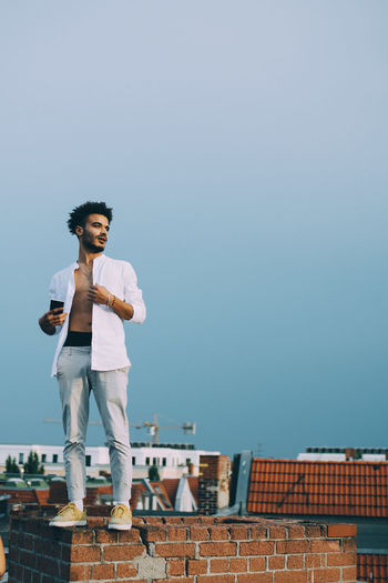 Man standing on roof against clear sky