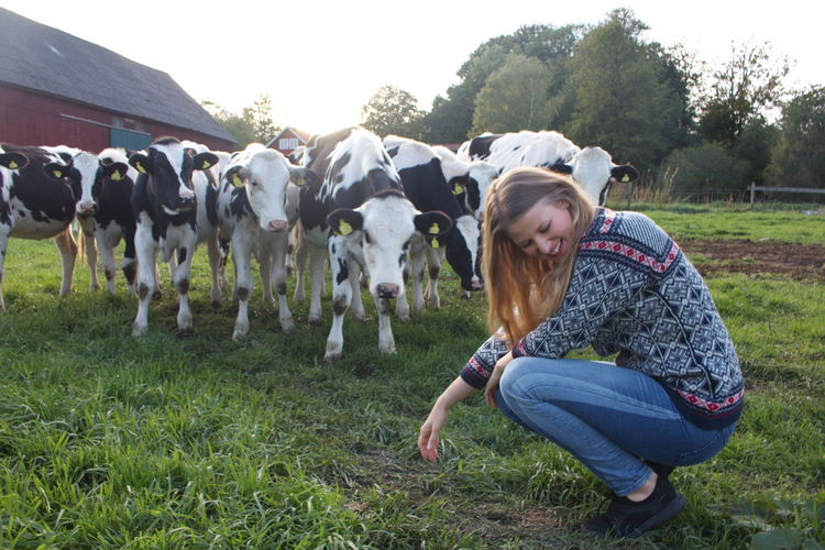 Smiling woman crouching by cows on field