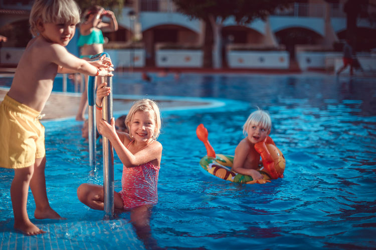 Boys Child Childhood Elementary Age Family Family With Two Children Fun Girls Happiness Leisure Activity Shirtless Smiling Swimming Pool Swimwear Water