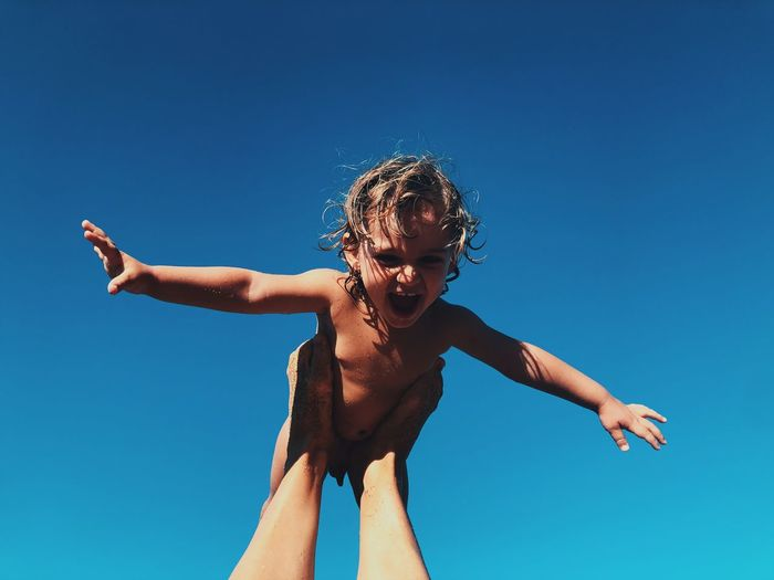 Low angle view of shirtless boy against blue sky