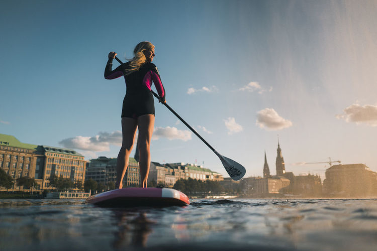 Woman standing on boat in city against sky