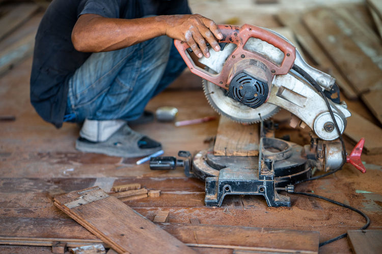 Adult Circular Saw Equipment Focus On Foreground Hand Tool Human Body Part Indoors  Machinery Mechanic Men Metal Occupation One Person Real People Skill  Tool Wheel Wood - Material Work Tool Working Workshop
