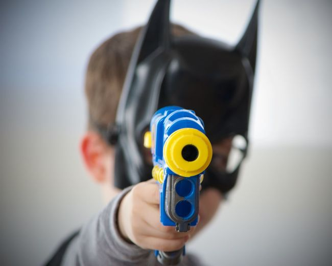 Close-up of boy shooting with toy handgun at home