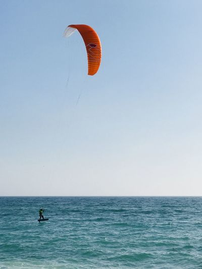 Person Kiteboarding In Sea Against Clear Sky