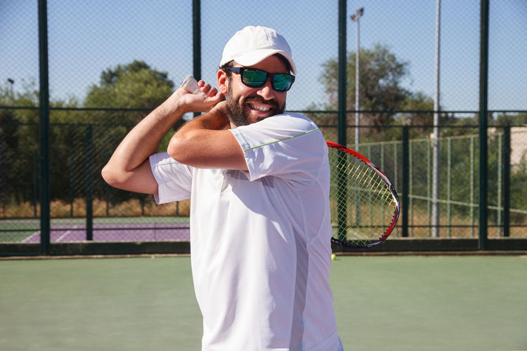 Smiling man playing tennis in court
