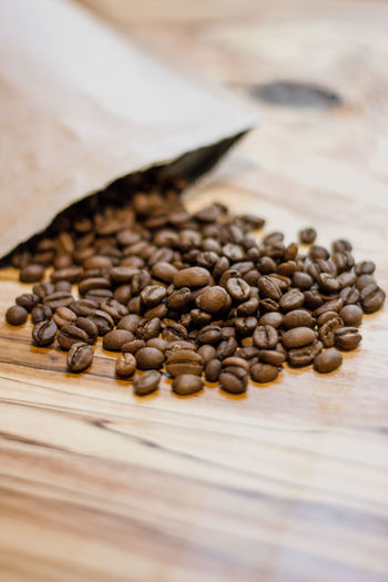 Food And Drink Still Life Food Table Freshness Indoors  Large Group Of Objects No People Brown Selective Focus Wood - Material Close-up Coffee - Drink Roasted Coffee Bean Coffee High Angle View Seed Spilling Roasted Abundance Caffeine Crockery