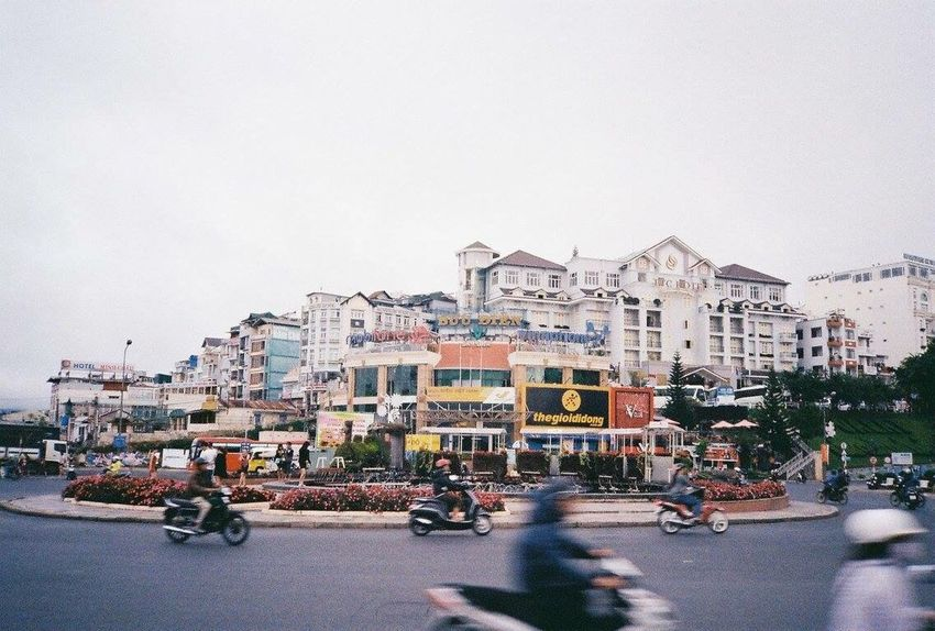 Vietnam Trip Architecture Building Exterior Built Structure City Transportation Street Olympus XA Film Film Photography Lifestyles Photography City Street Mode Of Transport City Life Road Streetphotography Streetphotothailand Bicycle Outdoors Motorcycle Clear Sky Sky Cityscape People