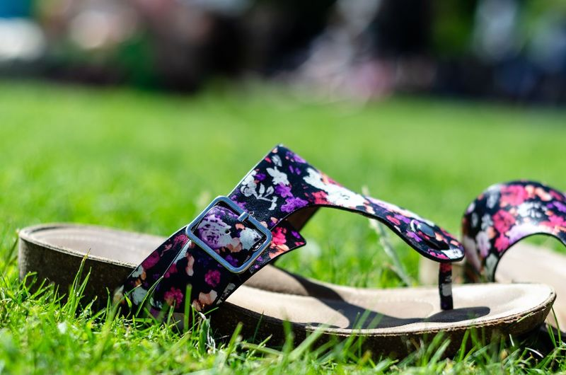 Colorful sandals on grass in summer
