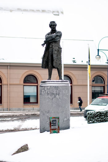 Statue against snow covered building