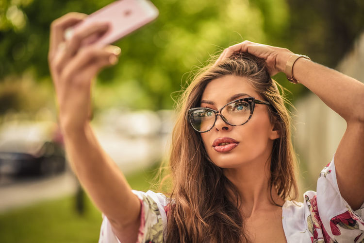 Young woman taking selfie with smart phone in park