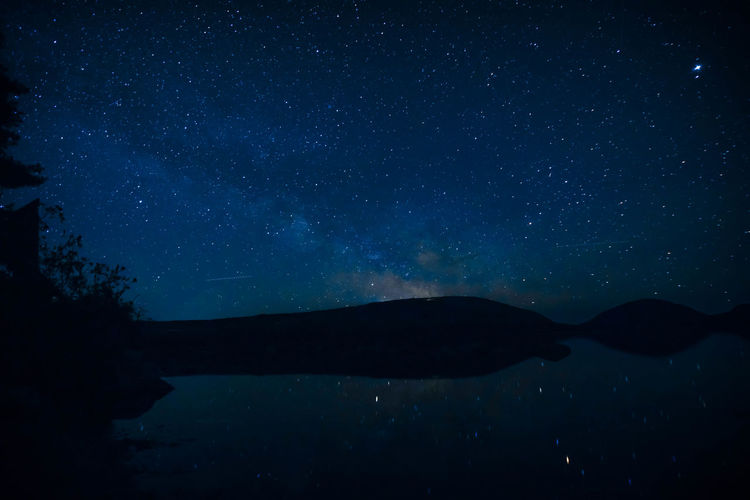 Scenic View Of Sea And Mountains Against Star Field In Sky At Night