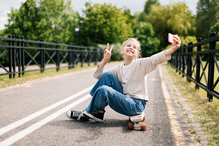 Cute blonde teenage girl sitting on a skateboard in a city park