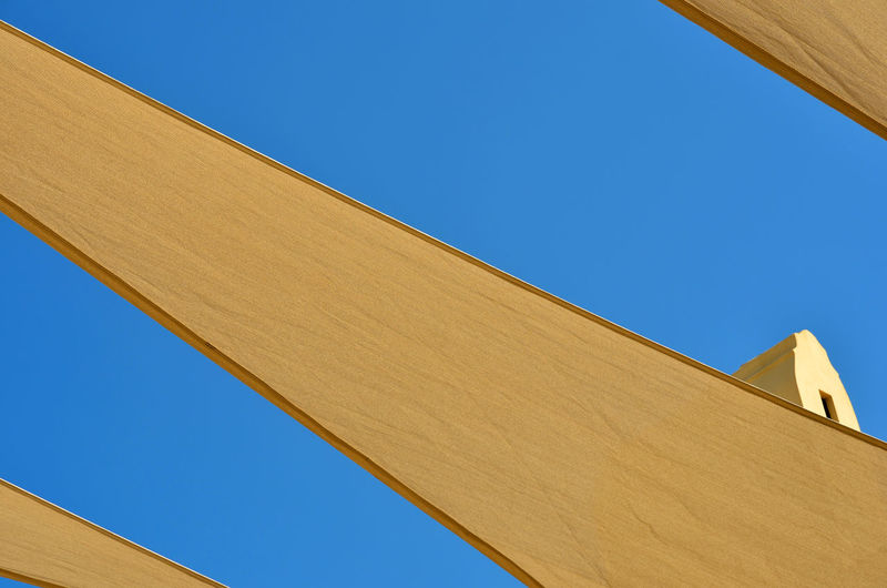 Low angle view of yellow fabrics hanging against clear blue sky