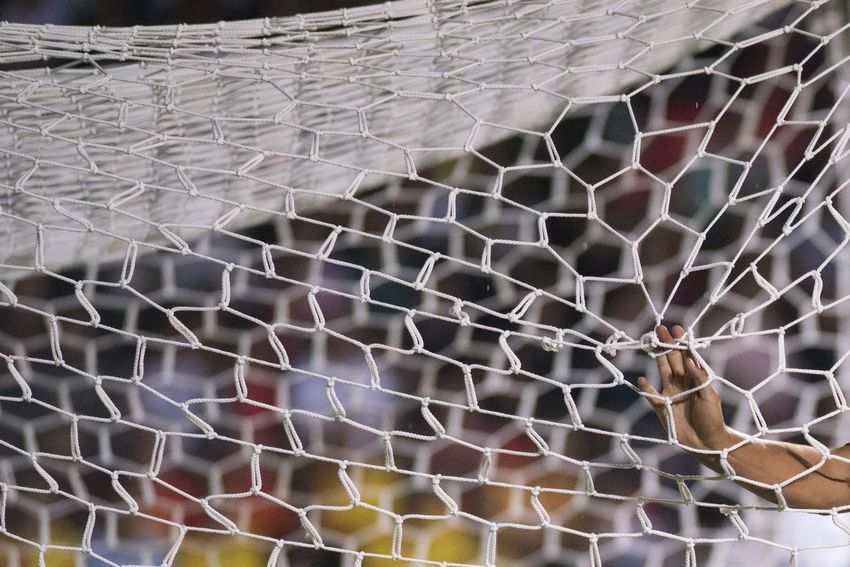 A soccer player holds the net of a goal. Arm Backgrounds Close-up Full Frame Human Body Part Net Outdoors Pattern Sports Textured