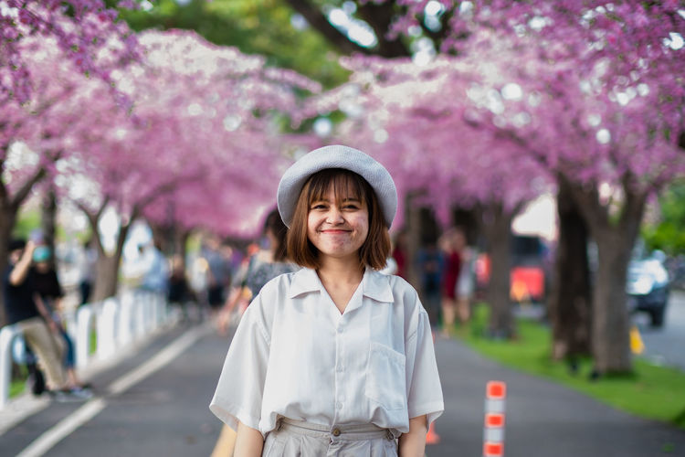 Portrait of beautiful young woman standing by cherry blossom