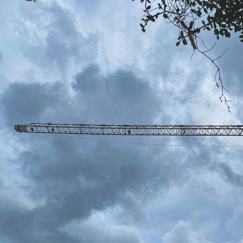 Low angle view of crane against sky