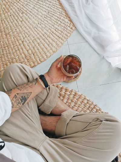 Midsection of man sitting with drink on floor