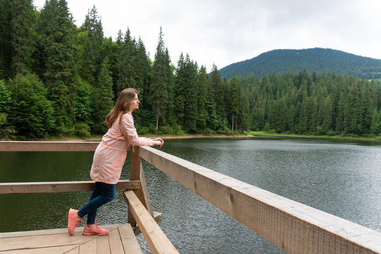 Full length of woman standing by lake against pine trees