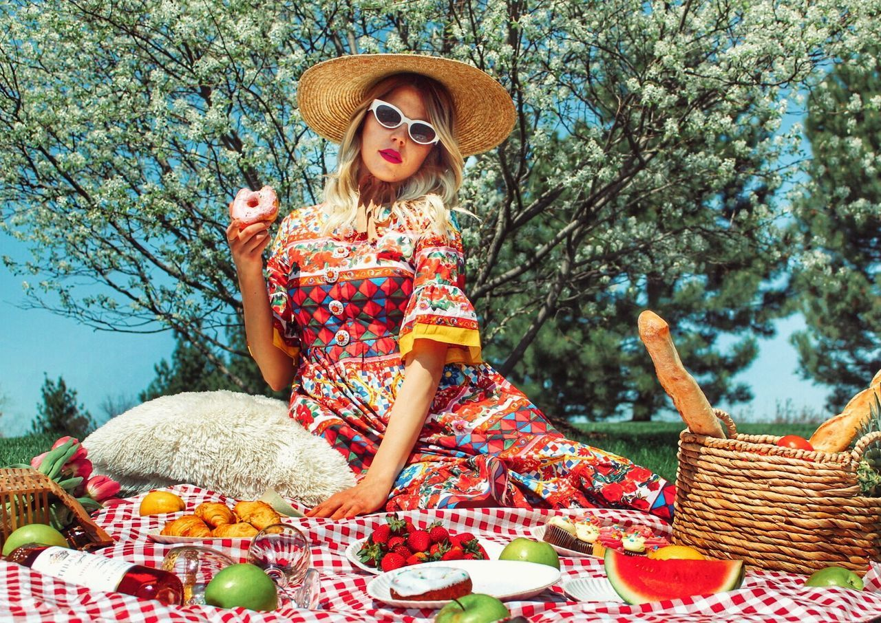 one person, clothing, hat, basket, adult, picnic, women, fashion, plant, smiling, container, young adult, day, nature, food and drink, food, sitting, front view, portrait, hair, beautiful woman, outdoors, sun hat, hairstyle