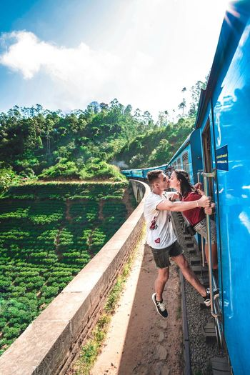 Young couple kissing while standing on passenger train doorway