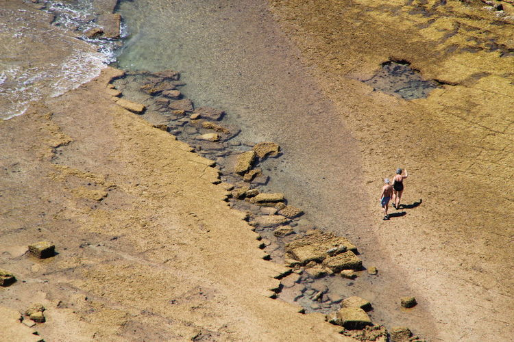 High angle view of couple walking on shore