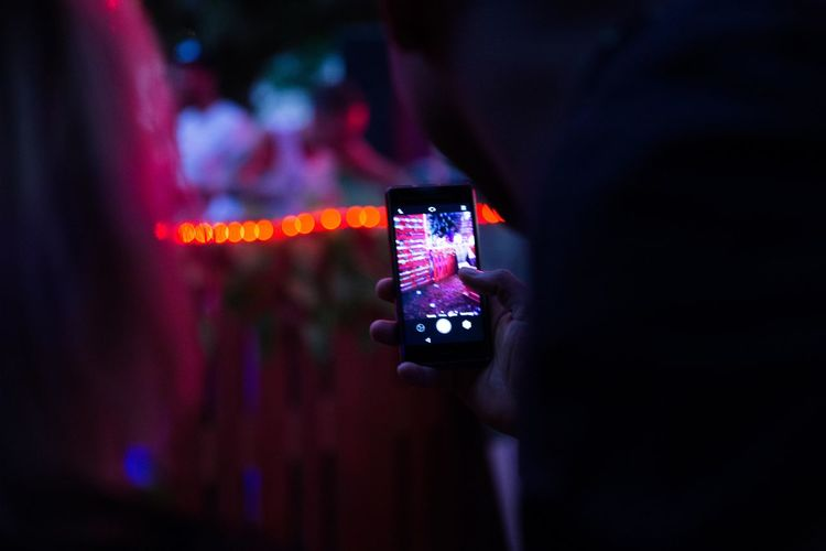 People photographing illuminated smart phone at night
