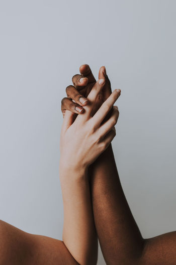 Cropped hands of women against gray background