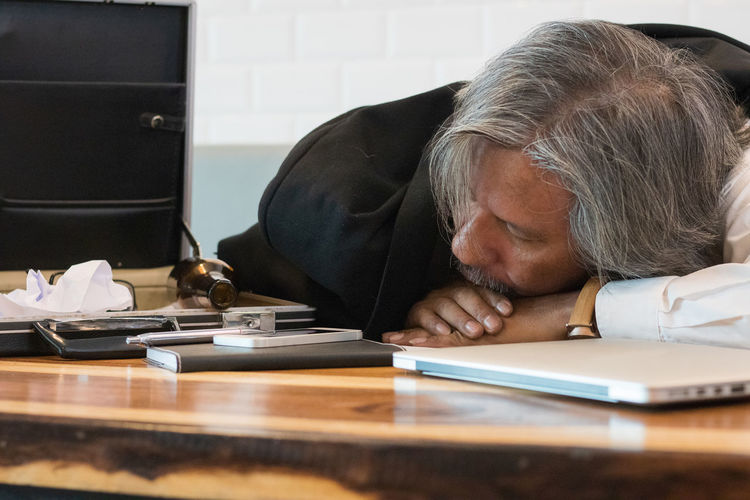 Drunken businessman sleeping on table in office