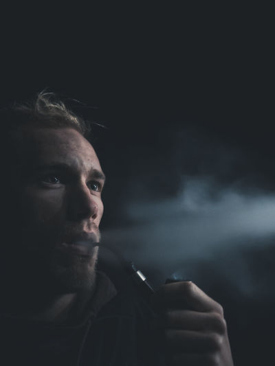 Close-up of young man smoking against black background