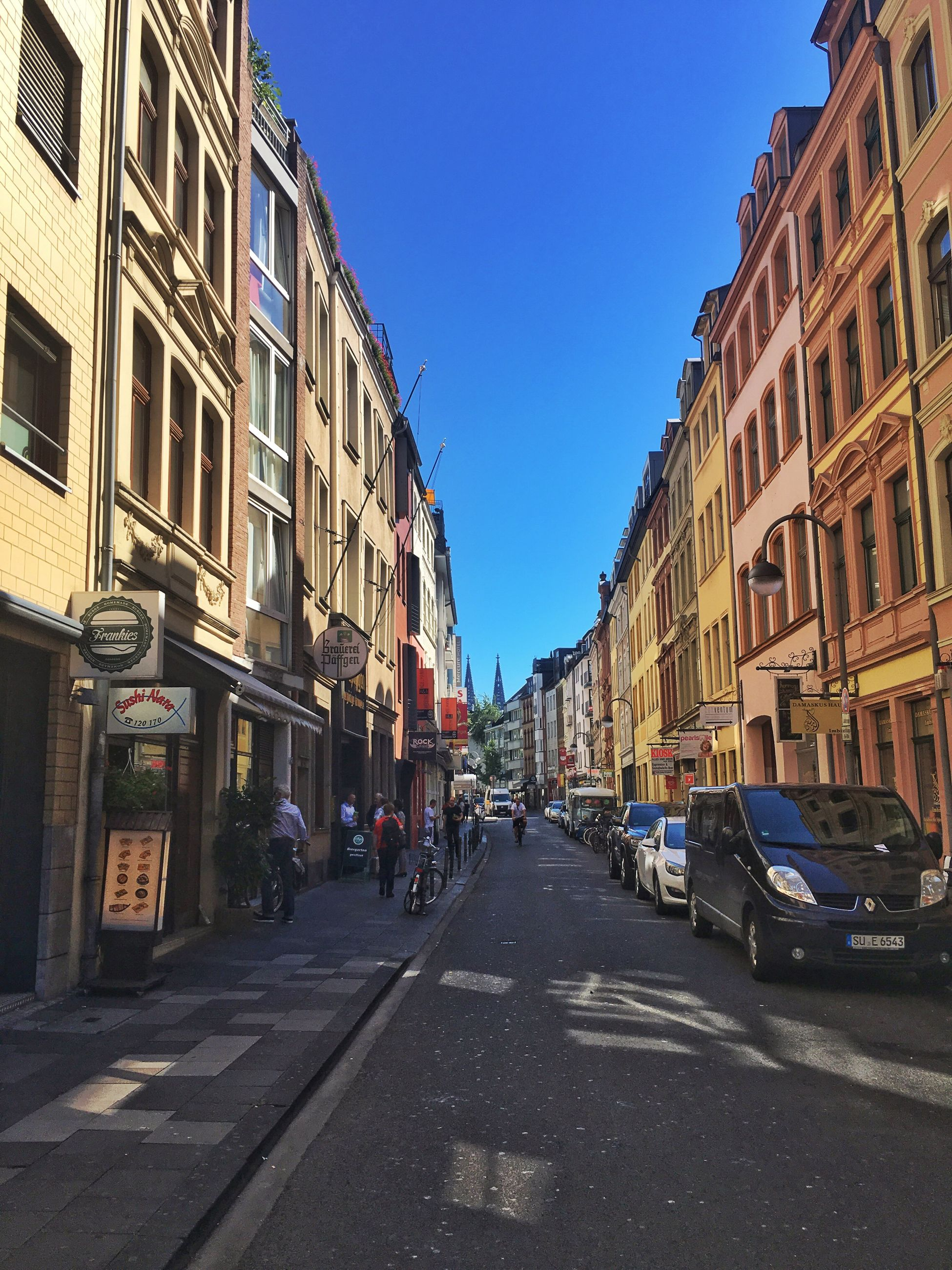 architecture, building exterior, built structure, transportation, city, street, car, clear sky, the way forward, road, city life, mode of transport, city street, residential structure, residential building, land vehicle, incidental people, blue, parking, diminishing perspective, residential district, day, outdoors, sunny, sky, vanishing point, in front of