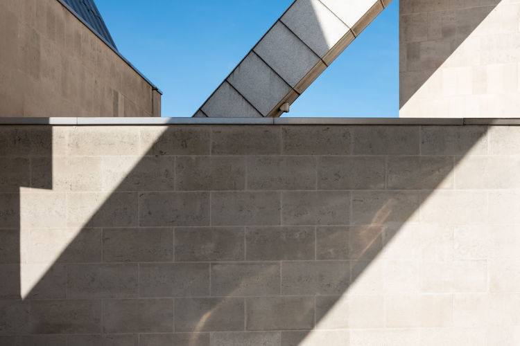Minimalist photo of geometric shapes created by sunlight, shadows and parts of a building.