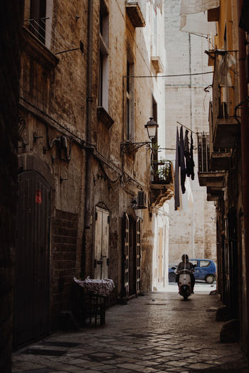 A man drive a scooter through an alleyway in Bari, Italy Bari Driving Hanging Man Moped Scooter Travel Alley Alleyway Architecture Blue Building Exterior Built Structure Car City Day Driving Around Drying Europe Italy Outdoors Small Travel Destinations Vintage Photo Wahsing