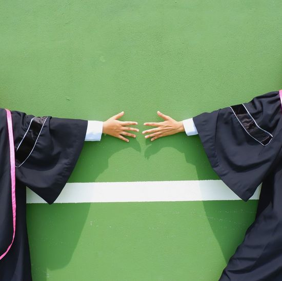 Midsection Of Students In Graduation Gowns Standing Against Wall