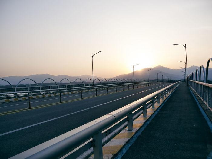 Bridge over street against sky during sunset
