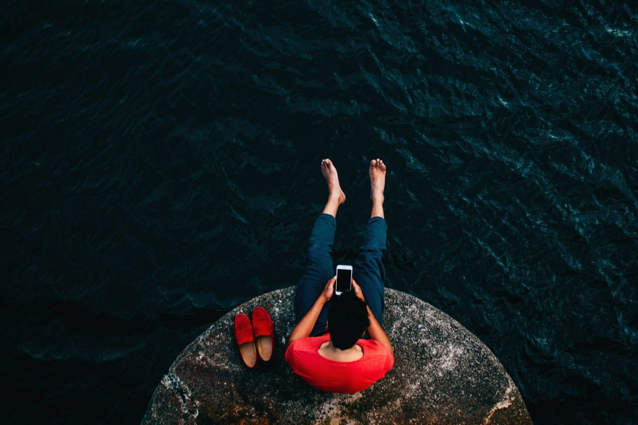 Man using mobile phone while sitting on rock at sea