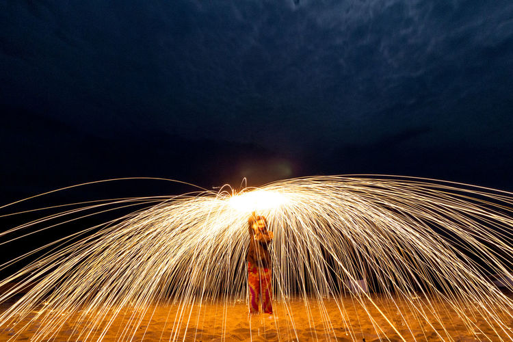 Womanwith Wire Wool Standing On Sand At Night