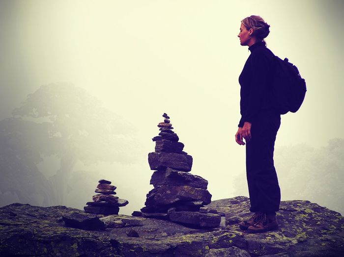 Side view full length of woman standing on mountain at inukshuk