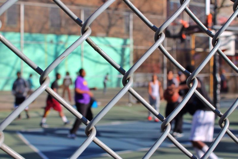 Men Playing Basketball Seen Through Chainlink Fence