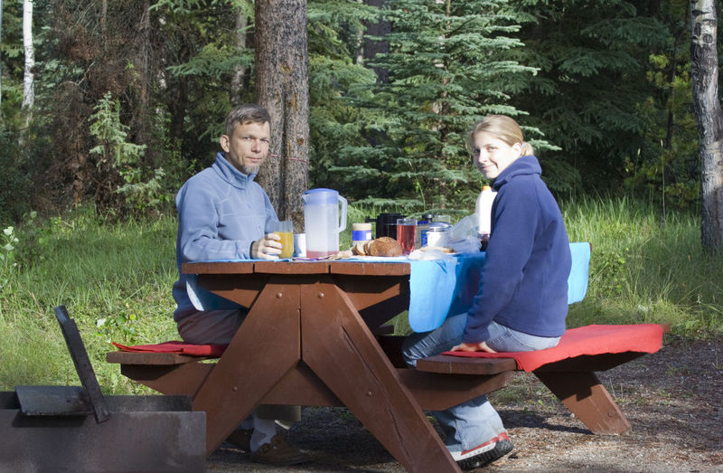 Portrait Of Father And Daughter Having Food And Drink On Picnic Table In Forest