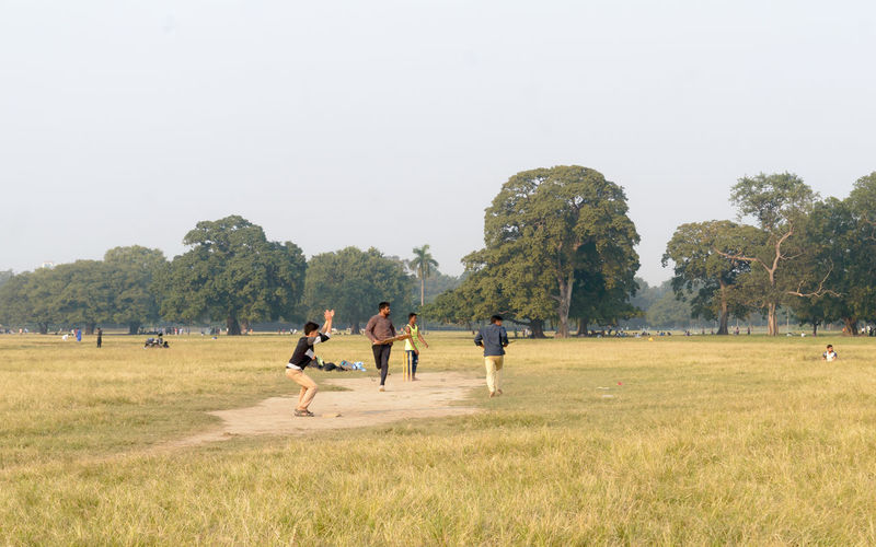 People playing on field against clear sky