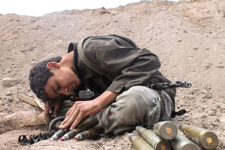 Boy sitting with gun on land