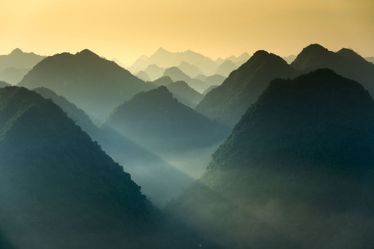 Scenic view of silhouette mountains during sunrise