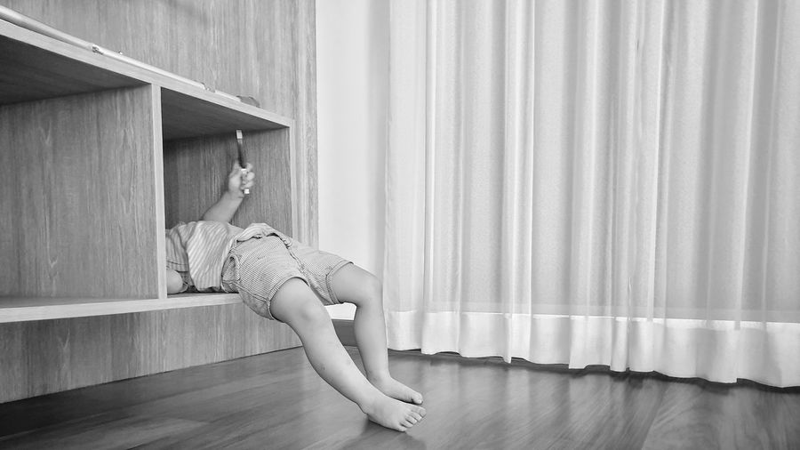 Low section of boy lying in shelf