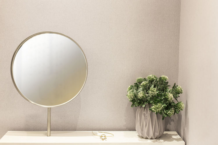Round mirror frame and House plant on white dressing table Plant Indoors  No People Wall - Building Feature Potted Plant Nature Table Geometric Shape Shape Day Growth Flower Circle Still Life Vase Mirror Close-up Home Interior Flowering Plant Green Color Flower Arrangement Round Mirror Makeup Dressing Table Stylish Text Luxury Mirror Lifestyles Female Care