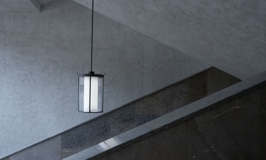 Low angle view of illuminated lamp on wall in building