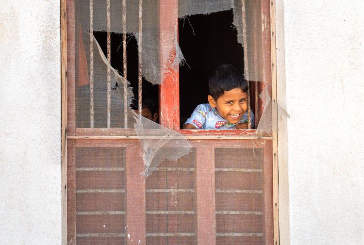Portrait of boy peeking through window