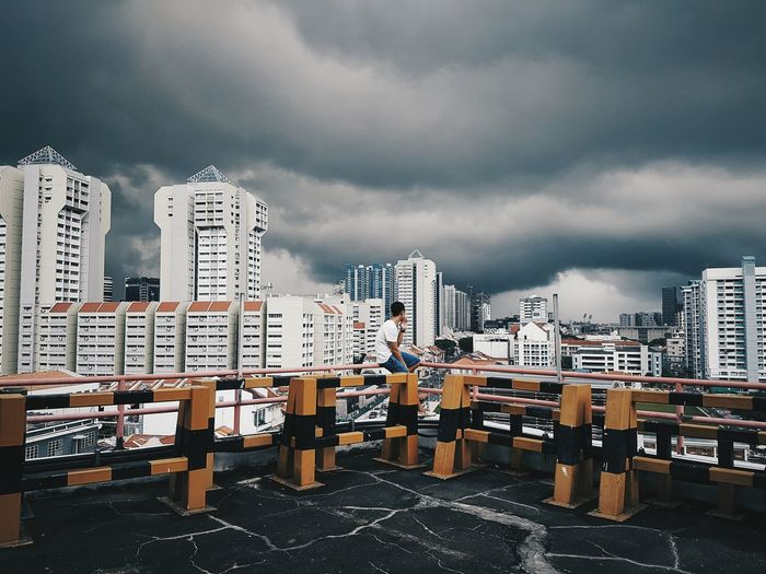 Man Sitting On Railing Of Building Terrace While Looking At Buildings Against Cloudy Sky