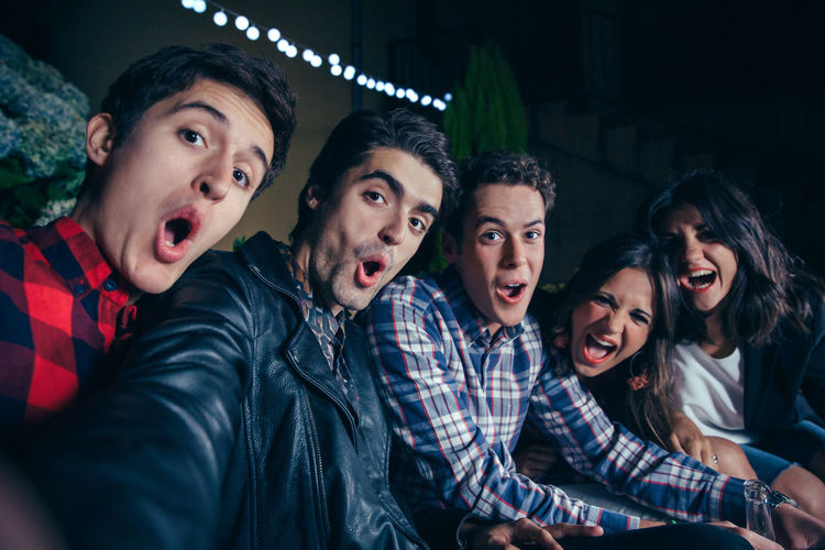 Group of funny young friends shouting while taking a selfie photo in a outdoors party. Friendship and celebrations concept. Celebration Friends Fun Happiness Happy Horizontal Looking At Camera Millenials Young Alcohol Cheerful Drink Entertainment Five People Friendship Grimace Group Night Nightlife Outdoors Party People Selfie Smiling Sofa